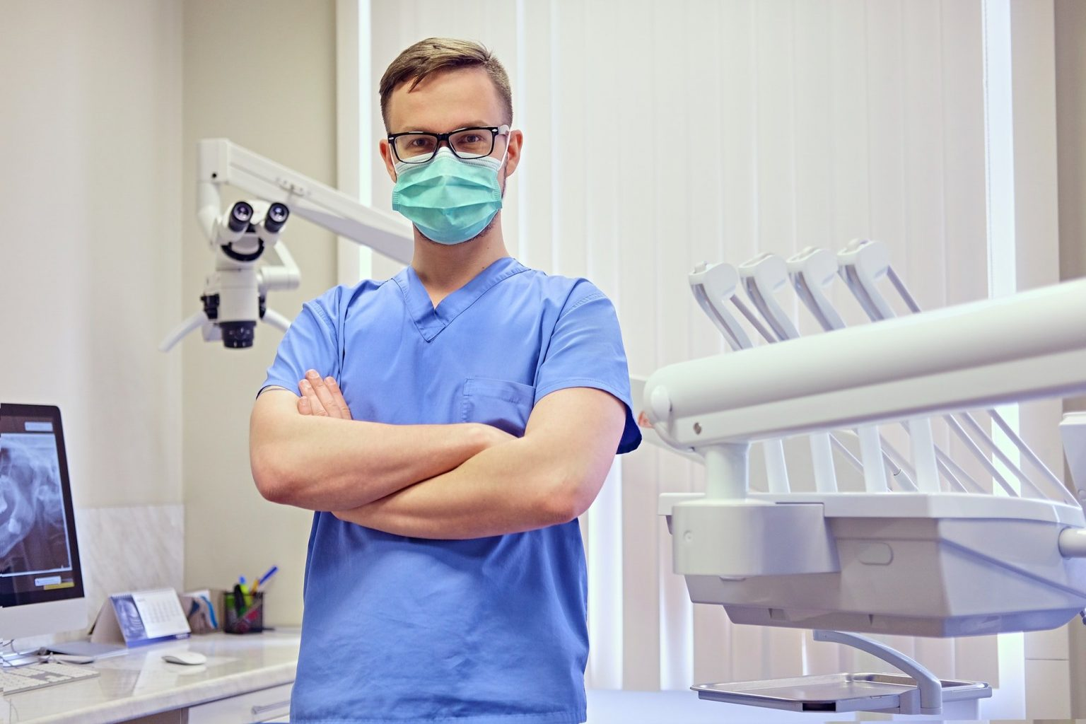 dentist in a room with medical equipment on background