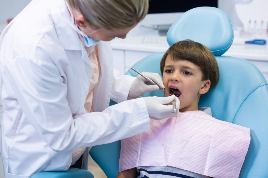 boy-receiving-dental-treatment-by-dentist-1.jpg
